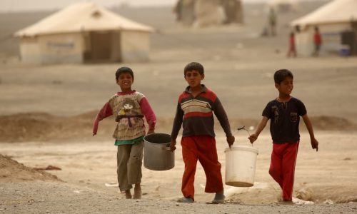 On 10 May 2017 in Karama camp, rural Ar-Raqqa in the Syrian Arab Republic, boys carry buckets to collect water.  Remethan, 10 (middle), and his family fled fighting in the village of Qadissya.  Everyday, Remethan joins his friends in the camp to collect water for his family.   ÒI just want to return home and live in a real house,Ó he says echoing the wish of other children living in the camp.   Intensified fighting in Ar-Raqqa in the recent months has forced an estimated 107,000 people, including 59,000 children, to flee their homes.  Most of them are staying in makeshift camps in the desert under basic conditions. UNICEF and partners are responding to meet the critical needs of the internally displaced children.  In Karama camp in the eastern countryside of Ar Raqqa where an estimated 40,000 people now live, UNICEF is trucking 600,000 litres of safe drinking water every day. UNICEF is also distributing much-needed hygiene and nutrition supplies to children and their families.